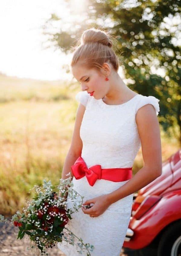 невеста в платье с алой лентой на талии